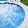 Blue jet spa pool in green grass garden — Stock Photo