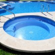 Blue jet spa pool in green grass garden - Stockfoto