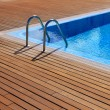 Stock Photo: Blue swimming pool with teak wood flooring