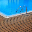 Blue swimming pool with teak wood flooring - Stock Photo