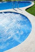 Blue jet spa pool in green grass garden — Stock Photo