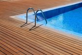 Blue swimming pool with teak wood flooring — Stock Photo