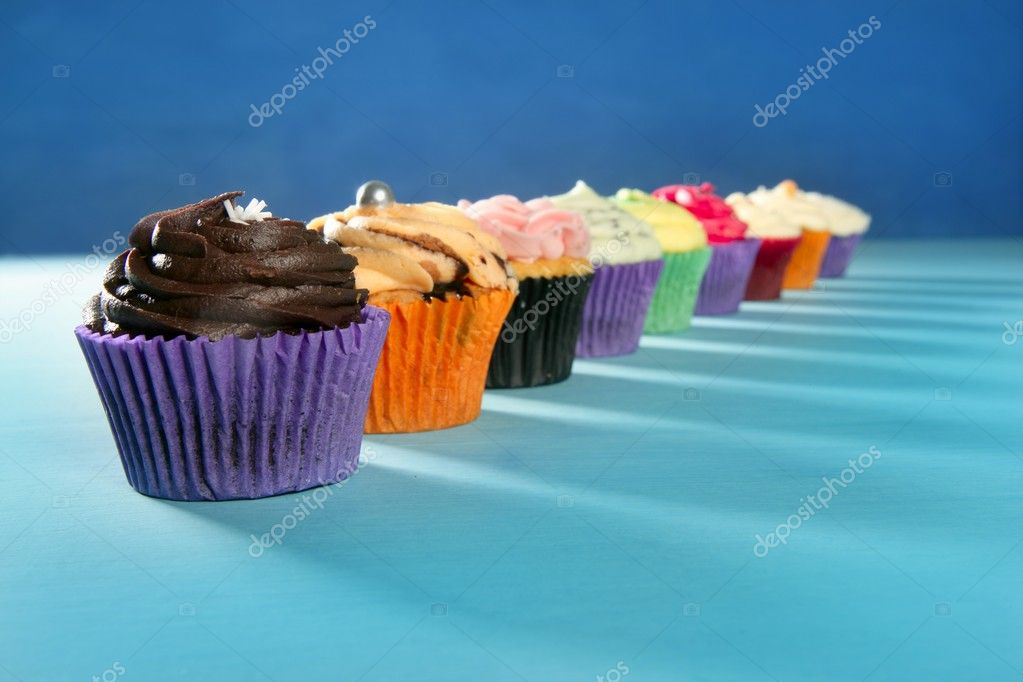 Cupcakes colorful cream muffin arrangement in a row line on turquoise — Stock Photo #5567264
