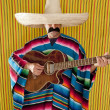 Mexican man serape poncho sombrero playing guitar — Stock fotografie