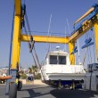 Stock Photo: Boat crane travelift lifting motorboat