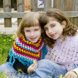 Children sister girls smiling in meadow spring fence — Stock Photo #5711577