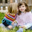 Children sister girls whisper in ear meadow spring — Stock Photo