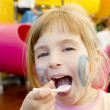 Eating spoon funny girl playground smiling blond — Stock Photo