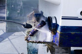 Blue boat hull cleaning pressure washer barnacles — Stock Photo