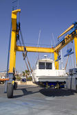 Boat crane travelift lifting motorboat — Stock Photo