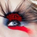 Black bird woman eye makeup macro red roses — Stock Photo