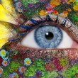 Foto Stock: Blue woman eye makeup spring flowers metaphor
