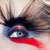 Black bird woman eye makeup macro beach sunrise — Stock Photo