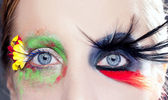 Asymmetrical fantasy eyes makeup spring black bird — Stock Photo