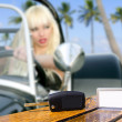 Car keys on table with blonde girl driving car in the beach — Stock Photo