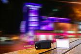 Car rental keys on wood table in night city lights — Stock Photo