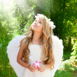 Angel children girl in forest with flower in hand - Stock Photo