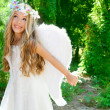 Angel children girl open arms in forest white wings - Stock Photo