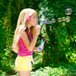 Children blowing soap bubbles in outdoor forest — Stock Photo #6214157