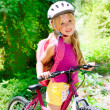 Stock Photo: Children girl riding bicycle outdoor in forest smiling