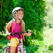 Children girl riding bicycle outdoor in forest smiling - ストック写真