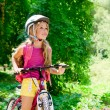 Children girl riding bicycle outdoor in forest smiling — Stock Photo #6214324
