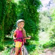 Children girl riding bicycle outdoor in forest smiling — Stock Photo #6214344