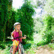 Children girl riding bicycle outdoor in forest smiling — Stock Photo #6214358