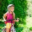 Children girl riding bicycle outdoor in forest smiling — Stock Photo