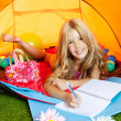 Children girl writing notebook in camping tent with flowers — ストック写真