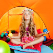 Foto Stock: Children girl inside camping tent relaxing with yoga