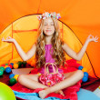 Blond little girl practicing yoga in orange camping tent - Stock Photo