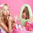 图库照片: Children fashion doll little girl lipstick makeup pink vanity