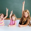 Kids student clever girls in classroom raising hand — Stock Photo