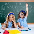 Clever nerd student girl in classroom raising hand - Stock Photo