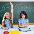 Photo: Clever nerd student girl in classroom raising hand