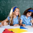 Classroom with two kids students cheating on test - Stock fotografie