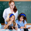 Kids students with nerd teacher woman at school — Stockfoto