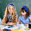 Children girls at school classroom with microscope — Stock Photo