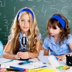 Children girls at school classroom with microscope — Stock Photo