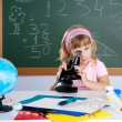 Children little girl at school classroom with microscope — Foto de stock #6218605
