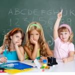 Boring sad student with clever children girl raising hand — Stock Photo