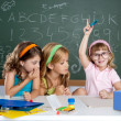 Stock Photo: Boring student with clever children girl raising hand