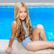 Blond children girl sittin in swimming pool border — Stock Photo #6219714