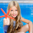 Children blond girl in summer vacation pool starfish — Stock Photo