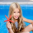 Children blond girl in summer vacation pool starfish — Stock Photo #6219948