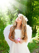 Angel children girl in forest with flower in hand — Stockfoto