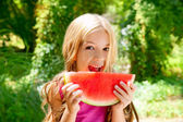 Children blond little girl eating watermelon slice in forest — Stock Photo