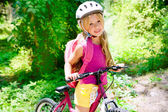 Children girl riding bicycle outdoor in forest smiling — Stok fotoğraf