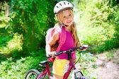 Děti dívka jedoucí na kole venkovní v lese s úsměvem — Stock fotografie